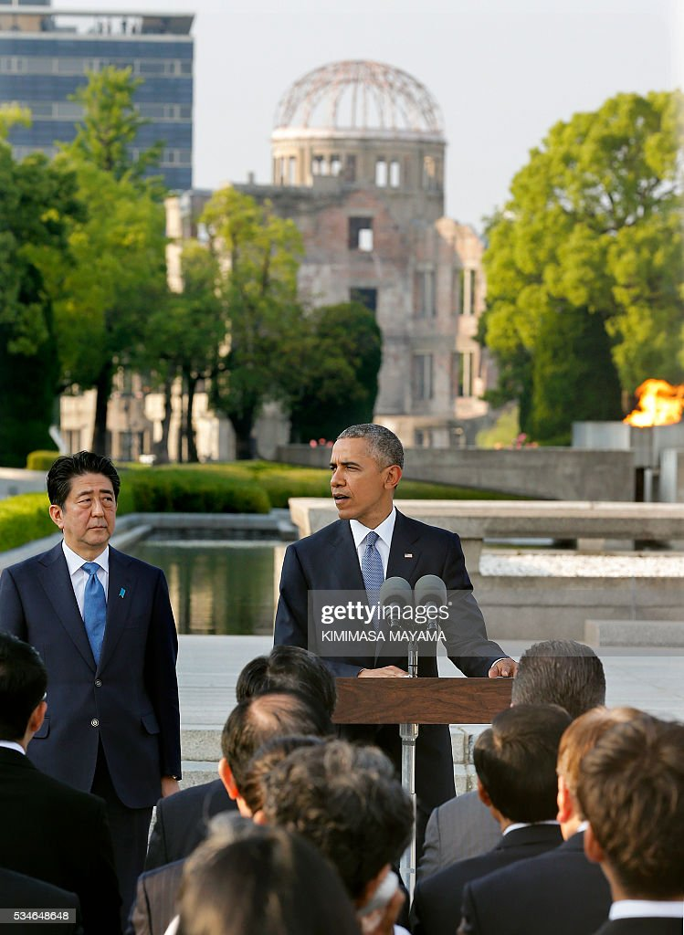 US Presdent Barack Obama (R) delivers his speech next to Japanese Prime Minister Shinzo Abe (L) after laying wreaths at the cenotaph to offer a prayer for victims of the atomic bombing in 1945, at Hiroshima Peace Memorial Park in Hiroshima on May 27, 2016. Obama on May 27 paid moving tribute to victims of the world's first nuclear attack. / AFP / POOL / KIMIMASA