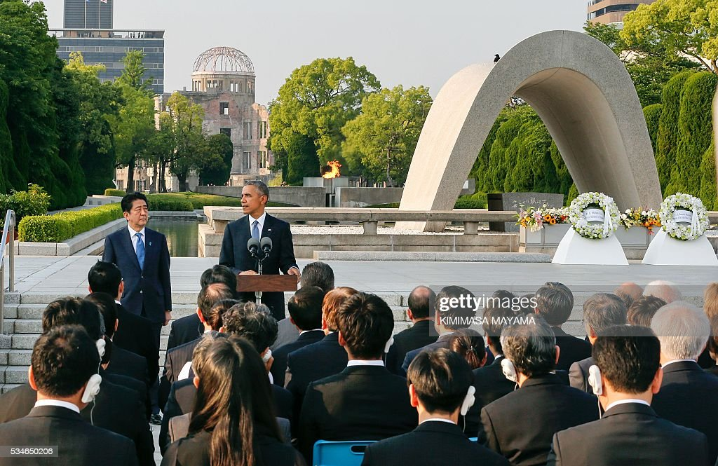 US President Barack Obama (2nd L) delivers his speech next to Japanese Prime Minister Shinzo Abe (L) after laying wreaths in front of a cenotaph to offer a prayer for victims of the atomic bombing in 1945, at Hiroshima Peace Memorial Park in Hiroshima on May 27, 2016. Obama on May 27 paid moving tribute to victims of the world's first nuclear attack. / AFP / POOL / KIMIMASA
