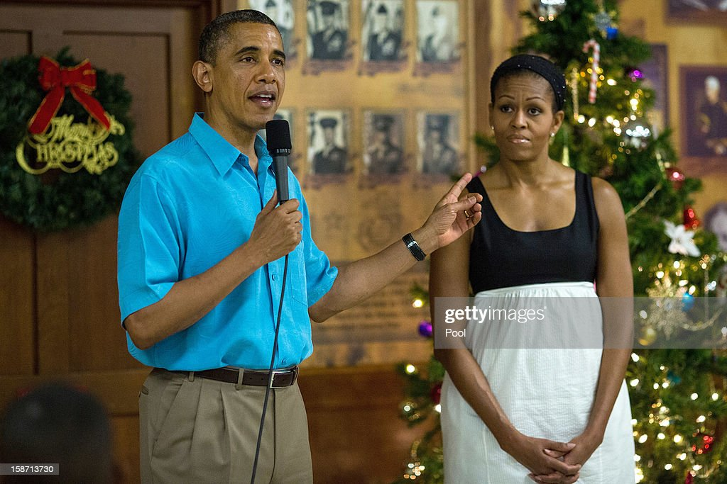 US President <a gi-track='captionPersonalityLinkClicked' href=/galleries/search?phrase=Barack+Obama&family=editorial&specificpeople=203260 ng-click='$event.stopPropagation()'>Barack Obama</a> delivers remarks while First Lady <a gi-track='captionPersonalityLinkClicked' href=/galleries/search?phrase=Michelle+Obama&family=editorial&specificpeople=2528864 ng-click='$event.stopPropagation()'>Michelle Obama</a> listens as they visited military personnel eating Christmas Dinner at Anderson Hall at Marine Corps Base Hawaii on December 25, 2012 in Kaneohe Bay, Hawaii. The president and his family spend the Christmas holiday in Hawaii, Obama's birthplace.