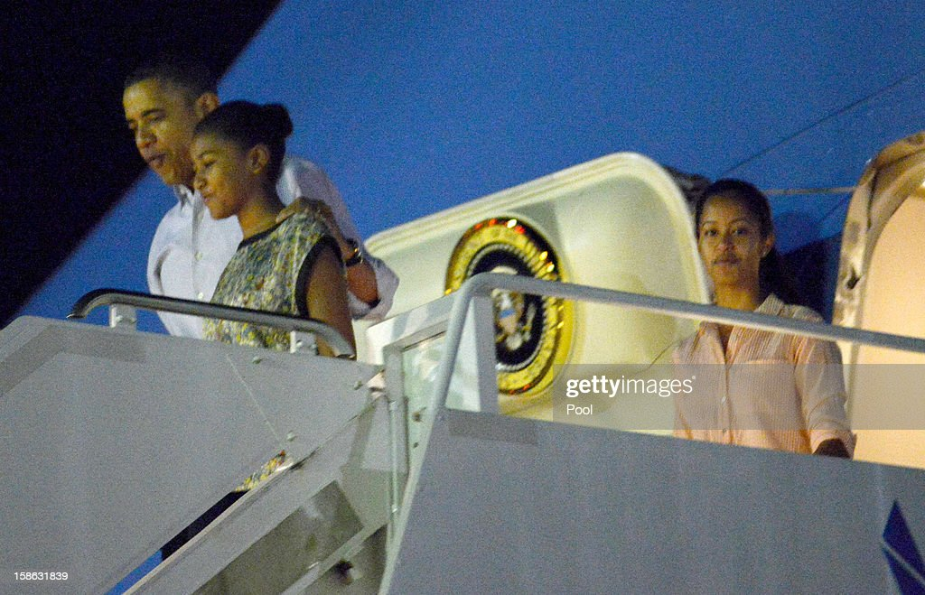 US President Barack Obama disembarks Obama Air Force One with daughters Natasha and Malia at Joint Base Pearl Harbor-Hickam on December 22, 2012 in Honolulu, Hawaii. Hawaii. The president and his family spend the Christmas holiday in Hawaii, Obama's birthplace.