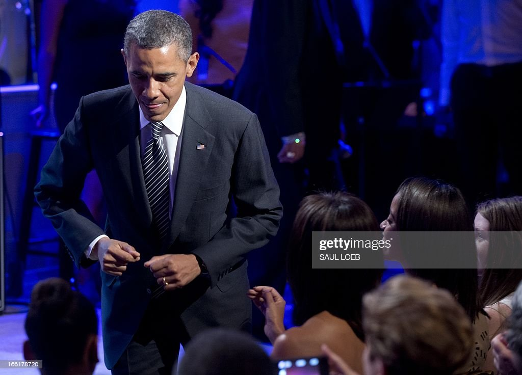 US President Barack Obama does a small dance move as he walks to his seat after speaking during a concert in honor of Memphis Soul music in the East Room of the White House in Washington, DC, on April 9, 2013, as part of the 'In Performance at the White House' series. The concert, featuring performances by Justin Timberlake, Booker T. Jones, Ben Harper, Queen Latifiah, among others, is the latest in the series that honors American musicians from all spectrums of musical genres, and airs next week on the PBS television channel. AFP PHOTO / Saul LOEB