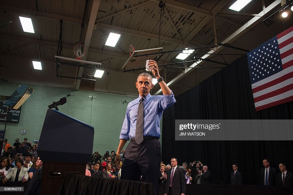 US President Barack Obama drinks a glass of water as he speaks at Flint Northwestern High School in Flint, Michigan, May 4, 2016 after meeting with locals for a neighborhood roundtable on the drinking water crisis. / AFP / Jim Watson