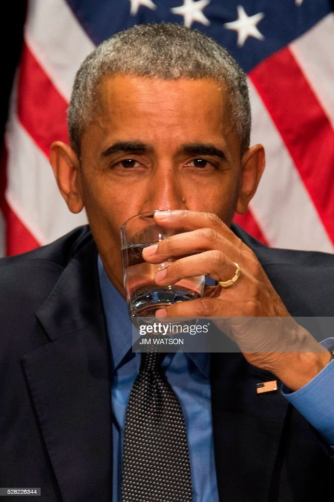 US President Barack Obama drinks filtered water during a meeting at the Food Bank of Eastern Michigan in Flint, Michigan, May 4, 2016. / AFP / Jim Watson