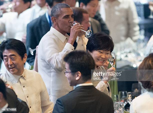US President Barack Obama drinks while next to Japan's Prime Minister Shinzo Abe and Abe's wife Akie as they attend the welcome dinner for leaders at...