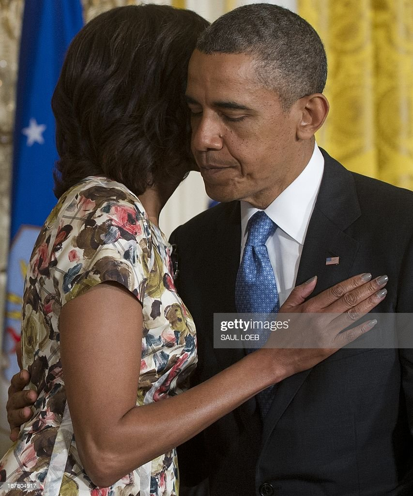 US President Barack Obama embraces First Lady Michelle Obama after speaking about the Joining Forces hiring initiative for military veterans and spouses in civilian jobs during an event in the East Room of the White House in Washington on April 30, 2013. Since President Obama challenged American businesses to hire US military veterans and spouses in August 2011, they have hired or trained 290,000 military veterans and spouses and now pledge to hire or train an additional 435,000 veterans and military spouses by 2018. AFP PHOTO / Saul LOEB