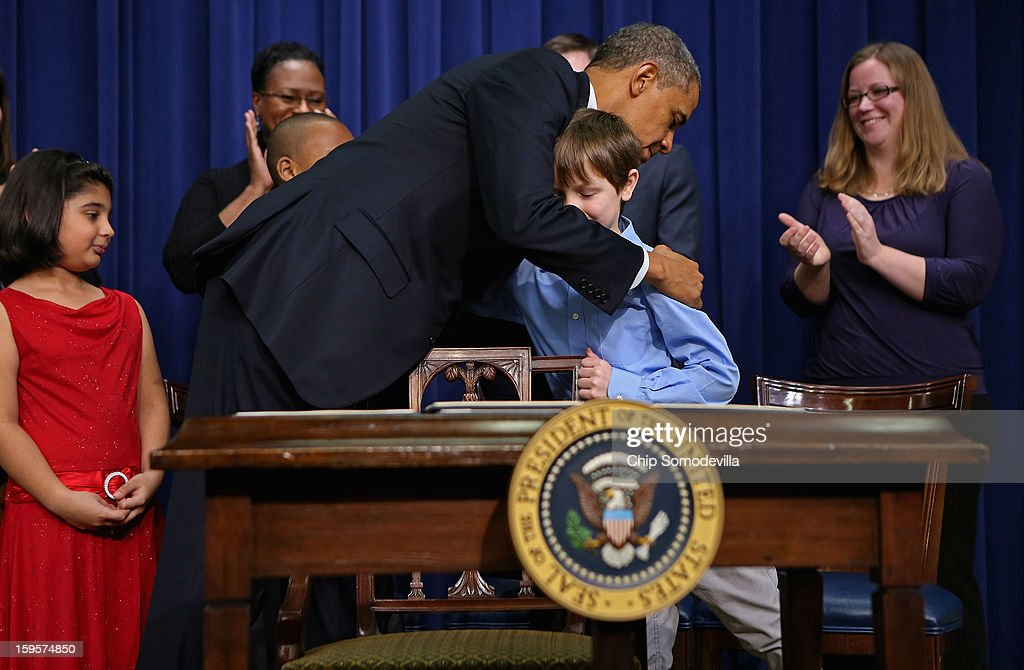 U.S. President Barack Obama embraces Grant Fritz and other children who wrote letters to the White House about gun violence after Obama signed a series of executive orders about the administraton's new gun law proposals in the Eisenhower Executive Office building January 16, 2013 in Washington, DC. One month after a massacre that left 20 school children and 6 adults dead in Newtown, Connecticut, the president unveiled a package of gun control proposals that include universal background checks and bans on assult weapons and high-capacity magazines.