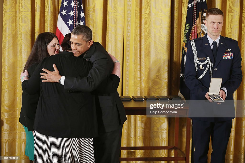 U.S. President <a gi-track='captionPersonalityLinkClicked' href=/galleries/search?phrase=Barack+Obama&family=editorial&specificpeople=203260 ng-click='$event.stopPropagation()'>Barack Obama</a> embraces Mary and Sarah D'Avino before presenting them with the 2012 Presidential Citizens Medal, the nation's second-highest civilian honor, on behalf of their sister and daughter, Rachel D'Avino in the East Room of the White House February 15, 2013 in Washington, DC. Rachel D'Avino, a behavioral therapist, was killed during a mass shooting that left 26 people dead at Sandy Hook Elementary School in December 2012. 'Their selflessness and courage inspire us all to look for opportunities to better serve our communities and our country,' Obama said about this year's recepients.