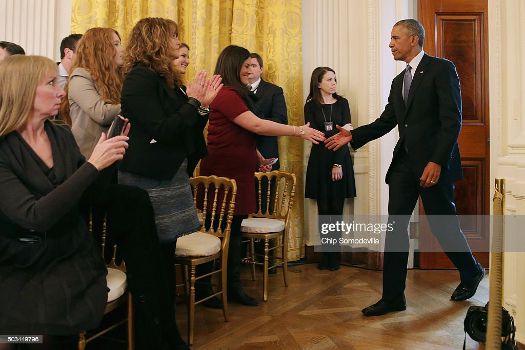 U.S. President Barack Obama (R) enters the East Room and greets victims of gun violence before delivering remarks about his efforts to increase federal gun control at the White House January 5, 2016 in Washington, DC. Without any approval from Congress, Obama is sidestepping the legislative process with executive actions to expand background checks for some firearm purchases and step up federal enforcement of existing gun laws.