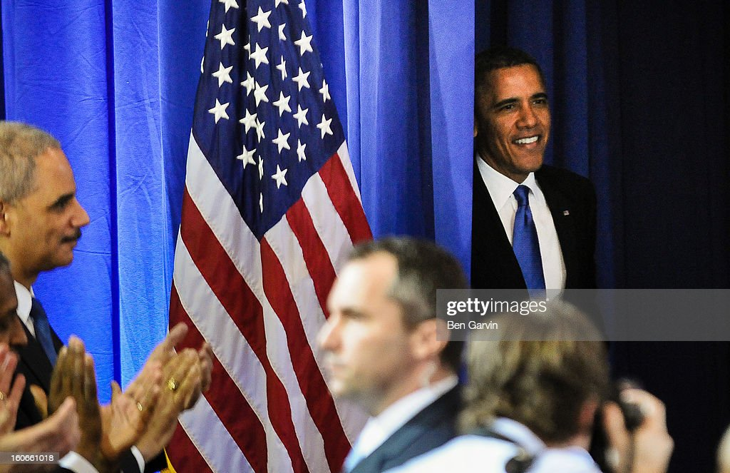 U.S. President <a gi-track='captionPersonalityLinkClicked' href=/galleries/search?phrase=Barack+Obama&family=editorial&specificpeople=203260 ng-click='$event.stopPropagation()'>Barack Obama</a> (R) enters the room as Attorney General <a gi-track='captionPersonalityLinkClicked' href=/galleries/search?phrase=Eric+Holder&family=editorial&specificpeople=1060367 ng-click='$event.stopPropagation()'>Eric Holder</a>, left, and others clap at the Minneapolis Police Department Special Operations Center on February 4, 2013 in Minneapolis, Minnesota. President Obama is promoting a ban on assault weapons and expanded background checks on gun buyers.