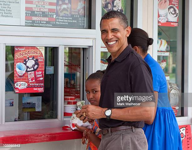 US President Barack Obama first lady Michelle Obama and 9 yearold daughter Sasha Obama stop at Bruster's Real Ice Cream August 15 2010 in Panama City...