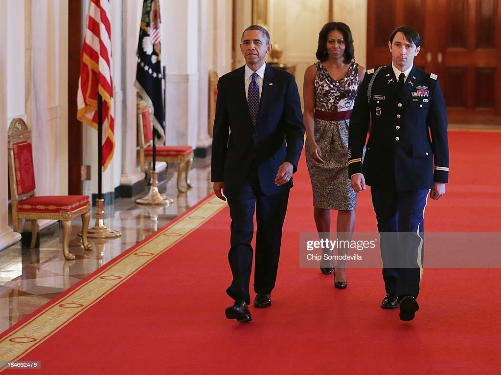 U.S. President Barack Obama, first lady Michelle Obama and and former U.S. Army Captain William Swenson arrive for the Medal of Honor ceremony in the East Room of the White House October 15, 2013 in Washington, DC. Honored for his actions in the 2009 Battle of Ganjgal Valley in the Kunar Province of Afghanistan, Swenson is the sixth living veteran of the Iraq and Afghanistan wars to receive the Medal of Honor, awarded to a person who 'distinguished himself conspicuously by gallantry and intrepidity at the risk of his life above and beyond the call of duty.'
