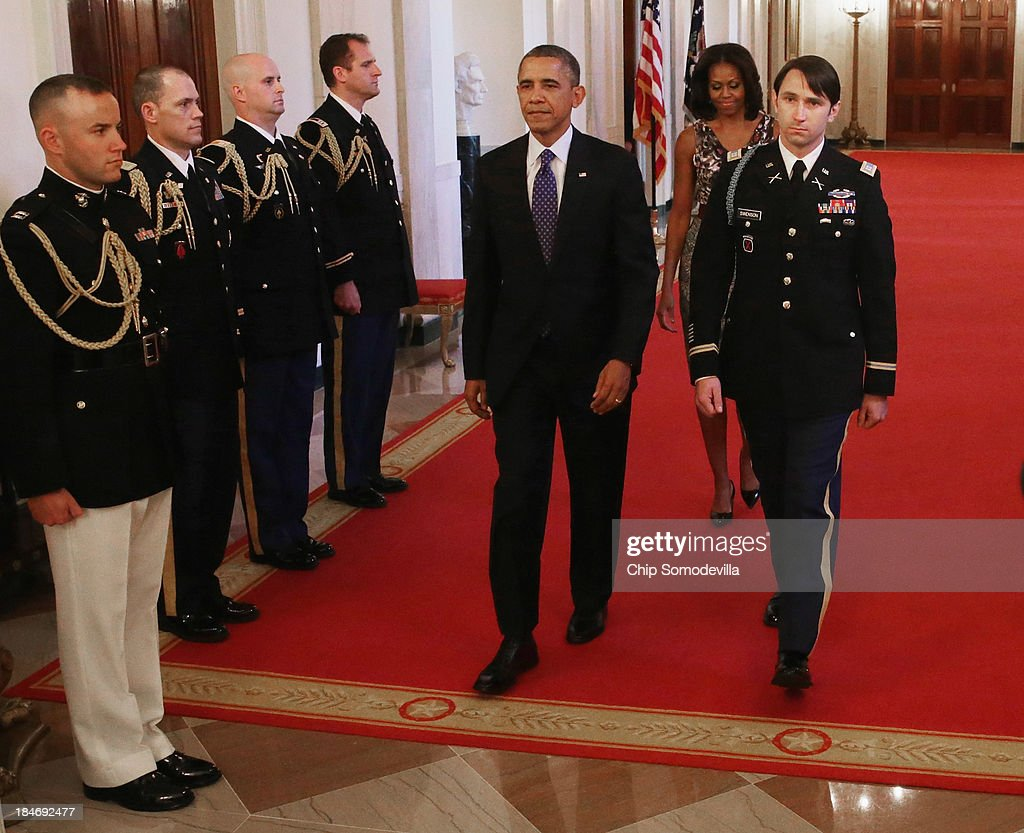 U.S. President Barack Obama (3rd R), first lady Michelle Obama (2nd R) and and former U.S. Army Captain William Swenson (R) arrive for the Medal of Honor ceremony in the East Room of the White House October 15, 2013 in Washington, DC. Honored for his actions in the 2009 Battle of Ganjgal Valley in the Kunar Province of Afghanistan, Swenson is the sixth living veteran of the Iraq and Afghanistan wars to receive the Medal of Honor, awarded to a person who 'distinguished himself conspicuously by gallantry and intrepidity at the risk of his life above and beyond the call of duty.'