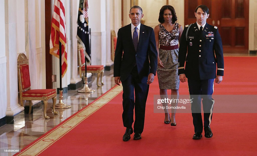 U.S. President <a gi-track='captionPersonalityLinkClicked' href=/galleries/search?phrase=Barack+Obama&family=editorial&specificpeople=203260 ng-click='$event.stopPropagation()'>Barack Obama</a>, first lady <a gi-track='captionPersonalityLinkClicked' href=/galleries/search?phrase=Michelle+Obama&family=editorial&specificpeople=2528864 ng-click='$event.stopPropagation()'>Michelle Obama</a> and and former U.S. Army Captain William Swenson arrive for the Medal of Honor ceremony in the East Room of the White House October 15, 2013 in Washington, DC. Honored for his actions in the 2009 Battle of Ganjgal Valley in the Kunar Province of Afghanistan, Swenson is the sixth living veteran of the Iraq and Afghanistan wars to receive the Medal of Honor, awarded to a person who 'distinguished himself conspicuously by gallantry and intrepidity at the risk of his life above and beyond the call of duty.'