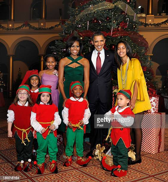 US President Barack Obama first lady Michelle Obama and daughters Malia and Sasha pose for a group photo with children dressed as elves prior to...