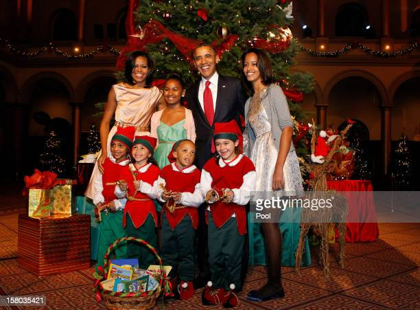US President Barack Obama first lady Michelle Obama and daughters Malia and Sasha greet Christmas elves as they attend the 'Christmas in Washington'...