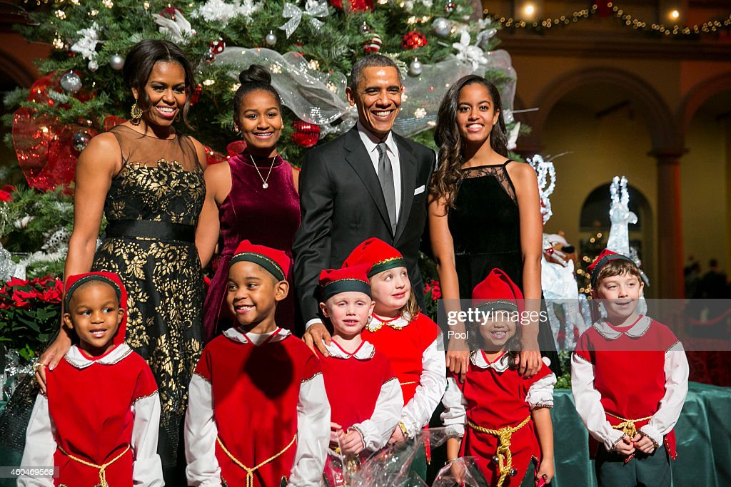 U.S. President Barack Obama (C, R), first lady Michelle Obama (L) and daughters Sasha (C,L) and Malia (R) pose with 'elves' prior to the taping of TNT's 'Christmas in Washington' program on December 14, 2014 in Washington, DC. The 'elves' are former patients of Children's National Medical Center, the beneficiary of this evenings concert.