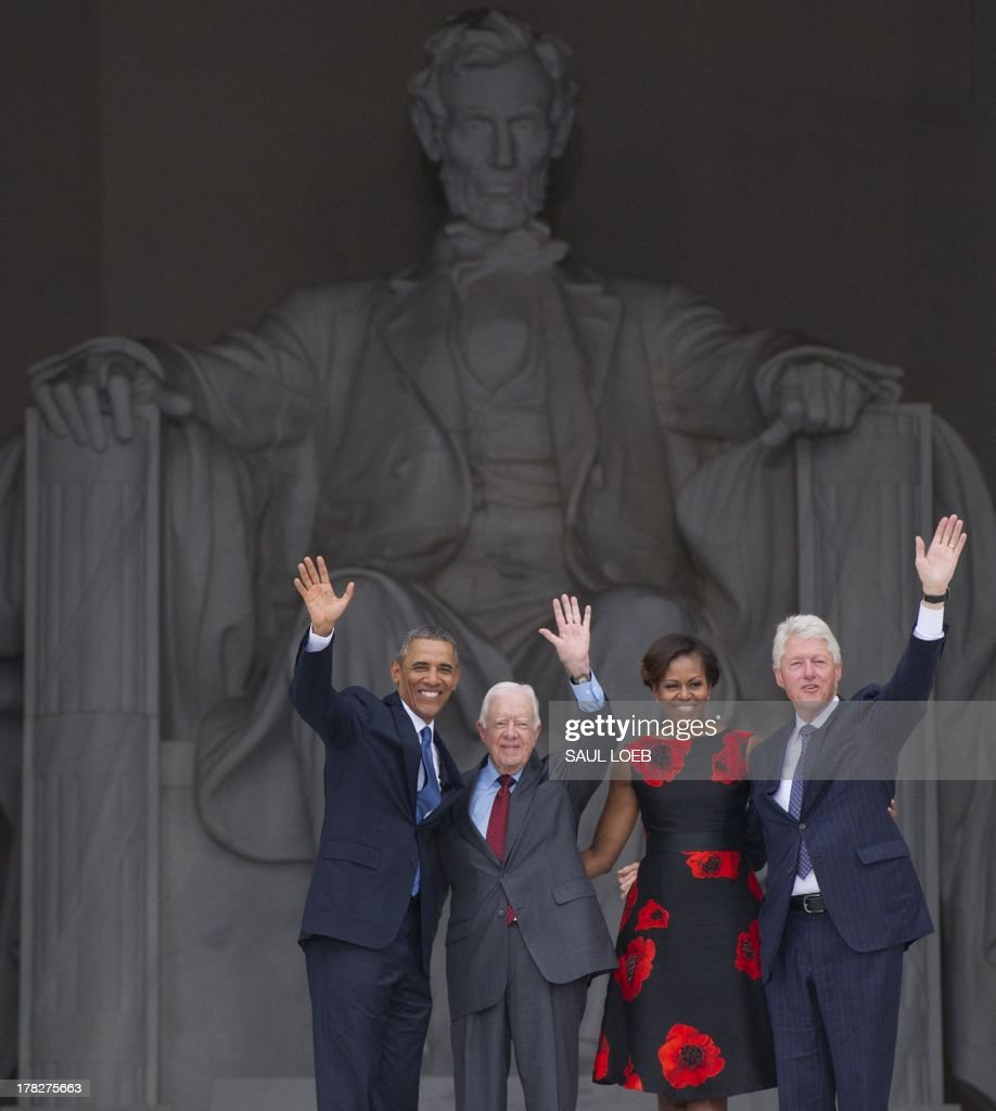 US President Barack Obama (L), First Lady Michelle Obama (2nd R) and former US Presidents Bill Clinton (R) and Jimmy Carter wave during the Let Freedom Ring Commemoration and Call to Action to commemorate the 50th anniversary of the March on Washington for Jobs and Freedom at the Lincoln Memorial in Washington, DC on August 28, 2013. Thousands will gather on the mall on the anniversary of the march and Dr. Martin Luther King, Jr.'s famous 'I Have a Dream' speech. AFP PHOTO / Saul LOEB