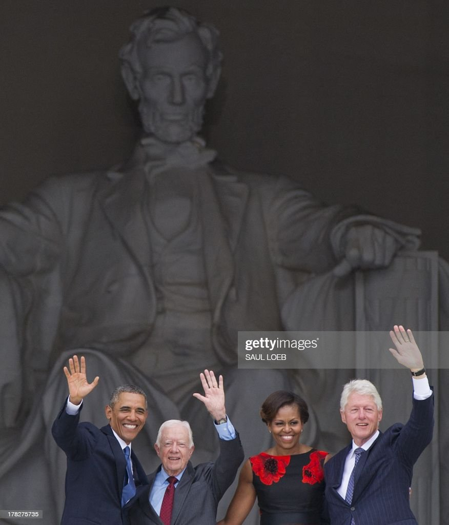 US President Barack Obama, First Lady Michelle Obama and former US Presidents Bill Clinton and Jimmy Carter wave during the Let Freedom Ring Commemoration and Call to Action to commemorate the 50th anniversary of the March on Washington for Jobs and Freedom at the Lincoln Memorial in Washington, DC on August 28, 2013. Thousands will gather on the mall on the anniversary of the march and Dr. Martin Luther King, Jr.'s famous 'I Have a Dream' speech. AFP PHOTO / Saul LOEB