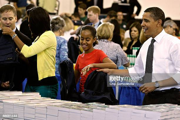 US President Barack Obama first lady Michelle Obama and their daughter Malia help stuff backpacks with books food and photographs of their dog Bo...