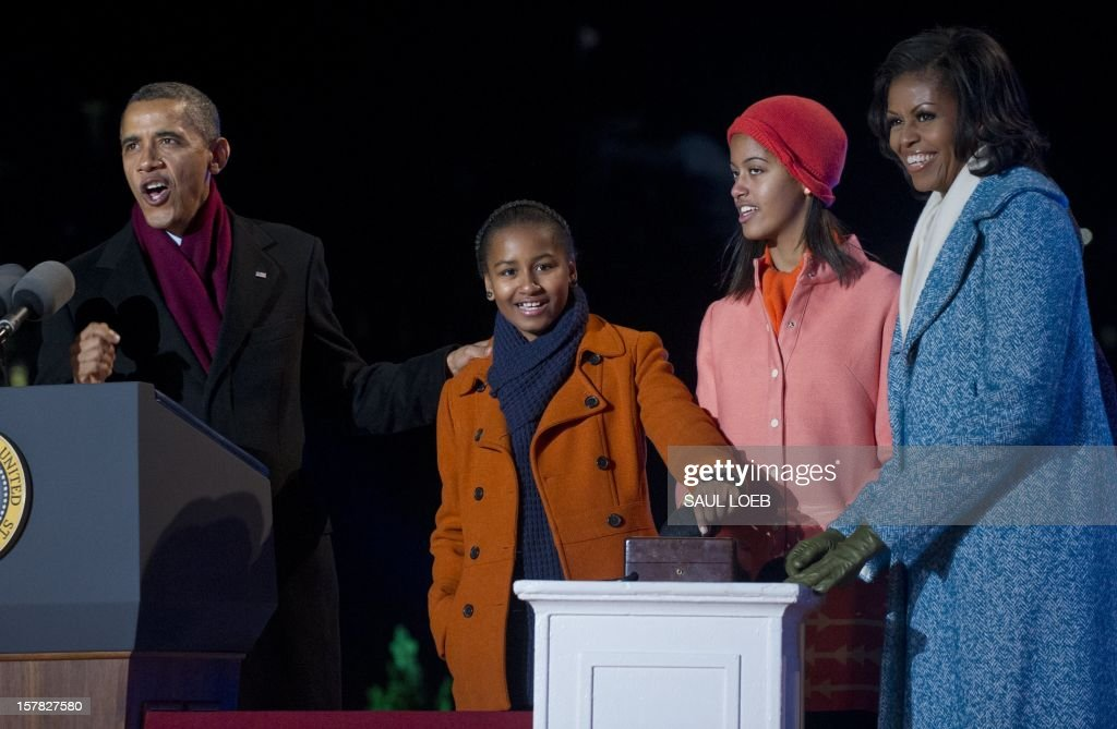 US President Barack Obama, First Lady Michelle Obama and their daughters, Sasha and Malia, prepare to push the button to light the National Christmas Tree during the National Christmas Tree Lighting on the Ellipse adjacent to the White House in Washington, DC, on December 6, 2012. The annual event, hosted by actor Neil Patrick Harris, features performances by Jason Mraz, Ledisi, James Taylor, Kenny 'Babyface' Edmonds, Colbie Caillat and American Idol season 11 winner Phillip Phillips. AFP PHOTO / Saul LOEB