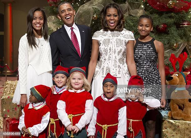 US President Barack Obama First Lady Michelle Obama and their daughters Sasha and Malia pose for photographs alongside children dressed as elves who...