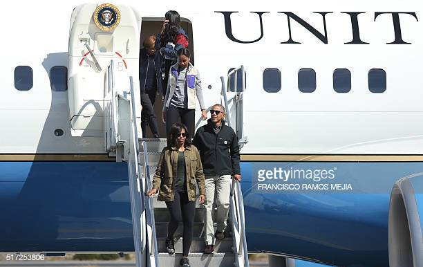 US President Barack Obama First Lady Michelle Obama and their daughters Malia and Sasha walk off the Air Force One upon their arrival at San Carlos...