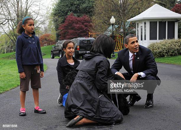 US President Barack Obama First Lady Michelle Obama and their daughters Malia and Sasha pose with the new puppy 'Bo' a Portuguese water dog April 14...