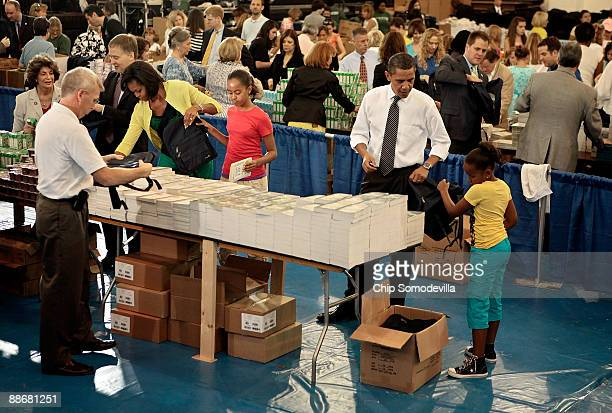 US President Barack Obama first lady Michelle Obama and their daughters Malia and Sasha help volunteers and members of Congress stuff backpacks with...