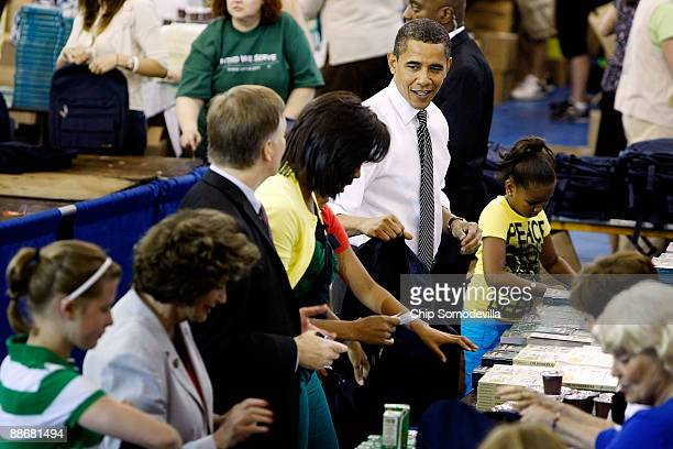 S President Barack Obama first lady Michelle Obama and their daughters Malia and Sasha help volunteers and members of Congress stuff backpacks with...