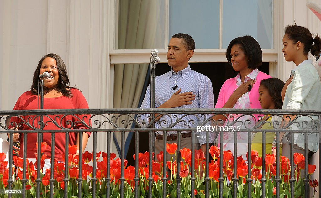 US President Barack Obama First Lady Michelle Obama and their daughters Sasha and Malia listen to TV show Glee's Amber Riley sing the national anthem...