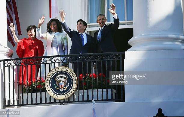 US President Barack Obama first lady Michelle Obama Japanese Prime Minister Shinzo Abe and his wife Akie Abe wave from the Truman Balcony during an...