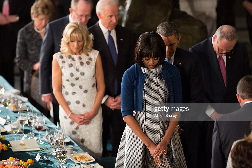 U.S. President Barack Obama, first lady Michelle Obama, Vice President Joe Biden and his wife Dr. Jill Biden, bow their heads during a prayer at the Inaugural Luncheon in Statuary Hall on inauguration day at the U.S. Capitol building January 21, 2013 in Washington D.C. Obama and Biden were ceremonially sworn in for their second term today.