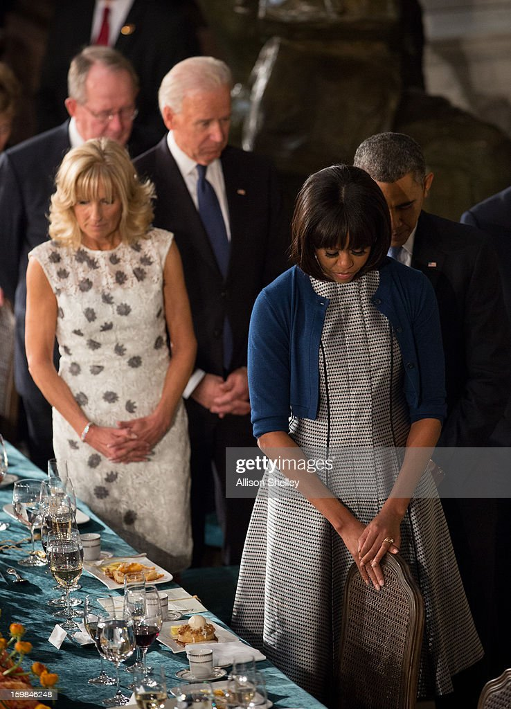U.S. President Barack Obama, first lady Michelle Obama, Vice President Joe Biden, his wife Dr. Jill Biden, bow their heads during a prayer at the Inaugural Luncheon in Statuary Hall on inauguration day at the U.S. Capitol building January 21, 2013 in Washington D.C. Obama and Biden were ceremonially sworn in for their second term today.