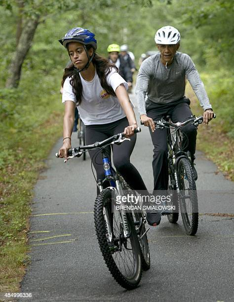 US President Barack Obama follows his daughter Malia during a bike ride on August 22 2015 in Vineyard Haven Massachusetts on Martha's Vineyard AFP...