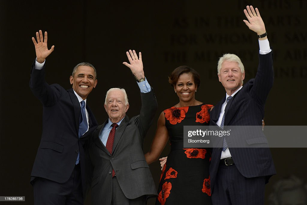 U.S. President Barack Obama, from left, former U.S. President Jimmy Carter, First Lady Michelle Obama, and former U.S. President Bill Clinton wave during the Let Freedom Ring commemoration event at the Lincoln Memorial in Washington, D.C., U.S., on Wednesday, Aug. 28, 2013. Obama, speaking from the same Washington stage where Martin Luther King Jr. delivered a defining speech of the civil rights movement, said that even as the nation has been transformed, work remains in countering growing economic disparities. Photographer: Michael Reynolds/Pool via Bloomberg