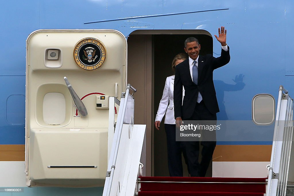 U.S. President Barack Obama, front, waves as he arrives with Hillary Clinton, U.S. secretary of state, at Yangon International Airport in Yangon, Myanmar, on Monday, Nov. 19, 2012. Obama hailed Myanmar's shift to democracy and urged more steps to increase freedom in the first visit to the former military regime by a U.S. president. Photographer: Dario Pignatelli/Bloomberg via Getty Images