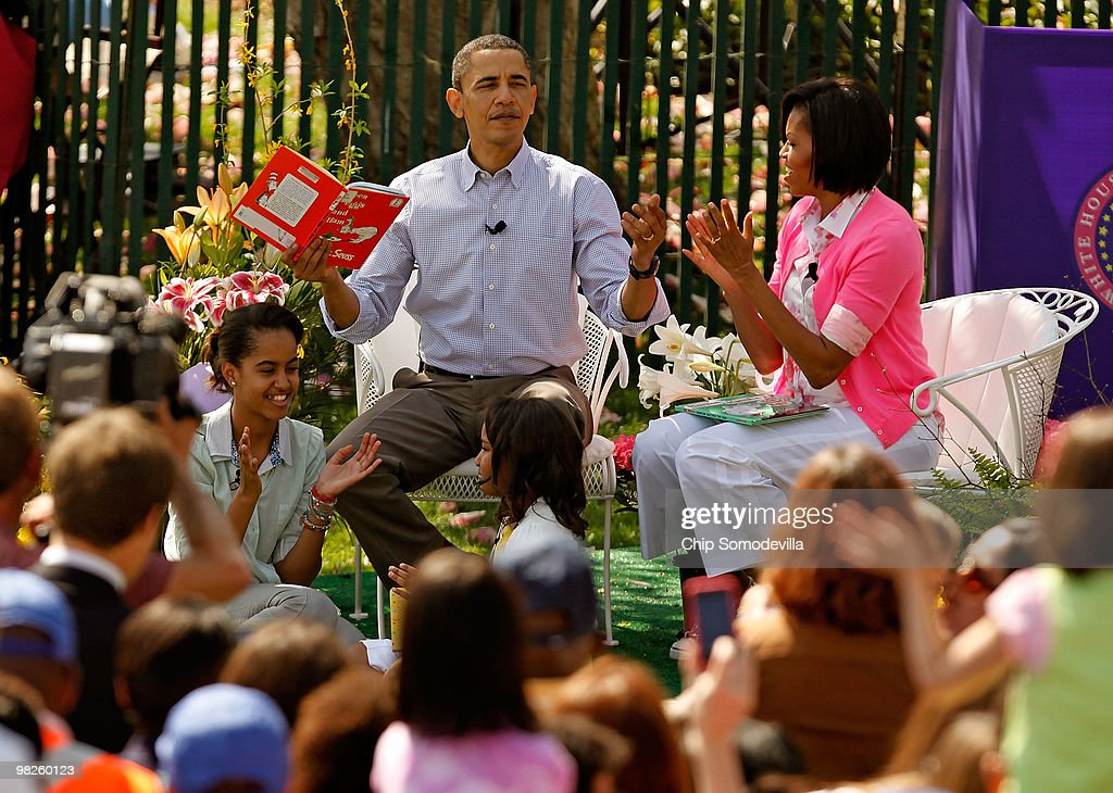 U.S. President Barack Obama (C) gets a round of applause after reading 'Green Eggs and Ham,' by Dr. Suess, for a group of children and his family, first lady Michelle Obama (R) and daughters Malia Obama (L), 11, and Sasha Obama, 8, during the Easter Egg Roll at the White House April 5, 2010 in Washington, DC. About 30,000 people are expected to attend attended the 132-year-old tradition of rolling colored eggs down the South Lawn of the White House.