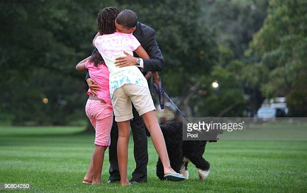 President Barack Obama gets a warm welcome home from daughters Sasha Malia and dog Bo on the South lawn of the White House September 15 2009 in...