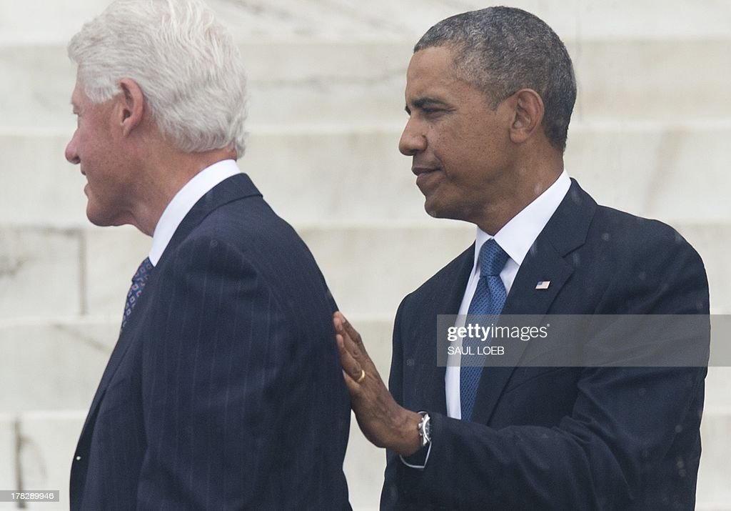 US President Barack Obama gives a pat on the back to former US President Bill Clinton (L) after speaking during the Let Freedom Ring Commemoration and Call to Action marking the 50th anniversary of the March on Washington for Jobs and Freedom at the Lincoln Memorial in Washington, DC on August 28, 2013. Thousands gathered on the mall on the anniversary of the march and Dr. Martin Luther King, Jr.'s famous 'I Have a Dream' speech. AFP PHOTO / Saul LOEB