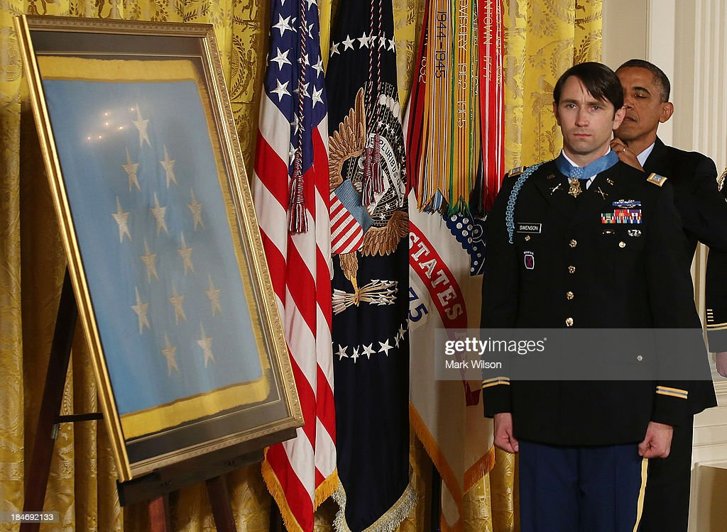 U.S. President Barack Obama (R) gives former U.S. Army Captain William Swenson the Medal of Honor during a ceremony in the East Room of the White House October 15, 2013 in Washington, DC. Honored for his actions in the 2009 Battle of Ganjgal Valley in the Kunar Province of Afghanistan, Swenson is the sixth living veteran of the Iraq and Afghanistan wars to receive the Medal of Honor, awarded to a person who 'distinguished himself conspicuously by gallantry and intrepidity at the risk of his life above and beyond the call of duty.'