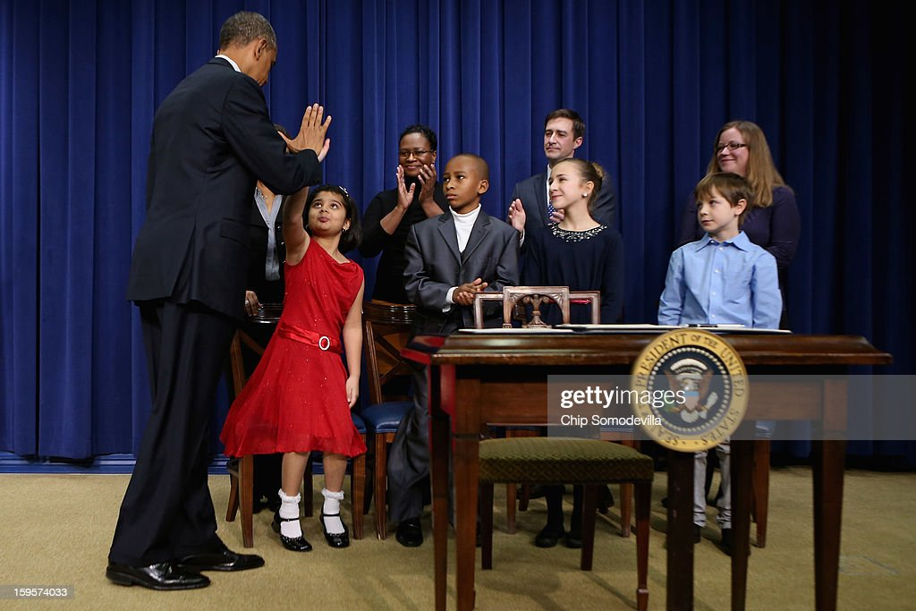 U.S. President Barack Obama (L) gives high-fives to children who wrote letters to the White House about gun violence, (L-R) Hinna Zeejah, Taejah Goode, Julia Stokes and Grant Fritz, after announcing the administration's new gun law proposals in the Eisenhower Executive Office building January 16, 2013 in Washington, DC. The president unveiled a package of gun control proposals that include universal background checks and bans on assault weapons and high-capacity magazines.