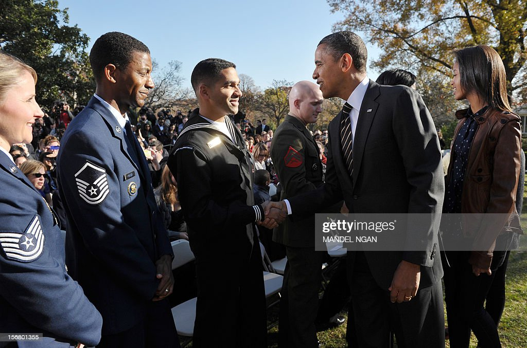 US President Barack Obama greet guests as his daughter Malia looks on after the annual Thanksgiving turkey pardon November 21 , 2012 at the Rose Garden of the White House in Washington, DC. Obama pardoned Cobbler and its alternate Gobbler, both raised in Rockingham County, Virginia. The turkeys will then spend the rest of the holiday season on display at George Washington's Mount Vernon estate. AFP PHOTO/Mandel NGAN