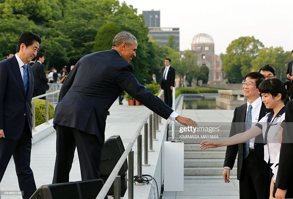 US President Barack Obama (C) greets a school student as Japanese Prime Minister Shinzo Abe watches (L) after delivering their speeches and laying wreaths in front of a cenotaph to offer a prayer for victims of the atomic bombing in 1945, at Hiroshima Peace Memorial Park in Hiroshima on May 27, 2016. Obama on May 27 paid moving tribute to victims of the world's first nuclear attack. / AFP / POOL / KIMIMASA