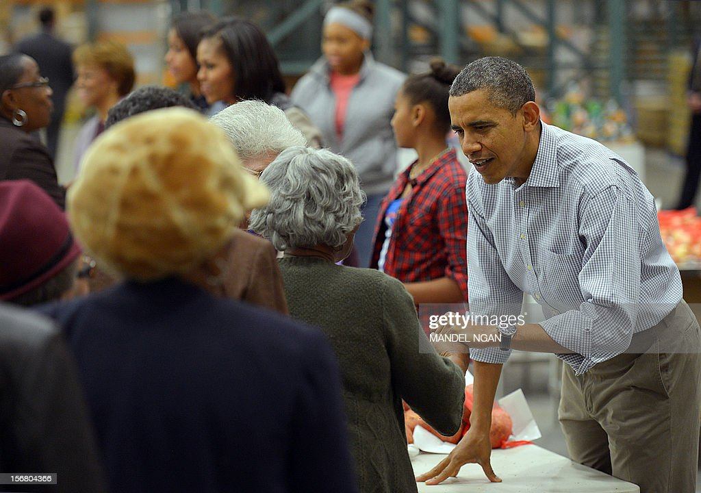 US President <a gi-track='captionPersonalityLinkClicked' href=/galleries/search?phrase=Barack+Obama&family=editorial&specificpeople=203260 ng-click='$event.stopPropagation()'>Barack Obama</a> greets a woman as he distributes food items at the Capitol Area Food Bank on November 21, 2012, a day ahead of Thanksgiving, in Washington, DC. AFP PHOTO/Mandel NGAN