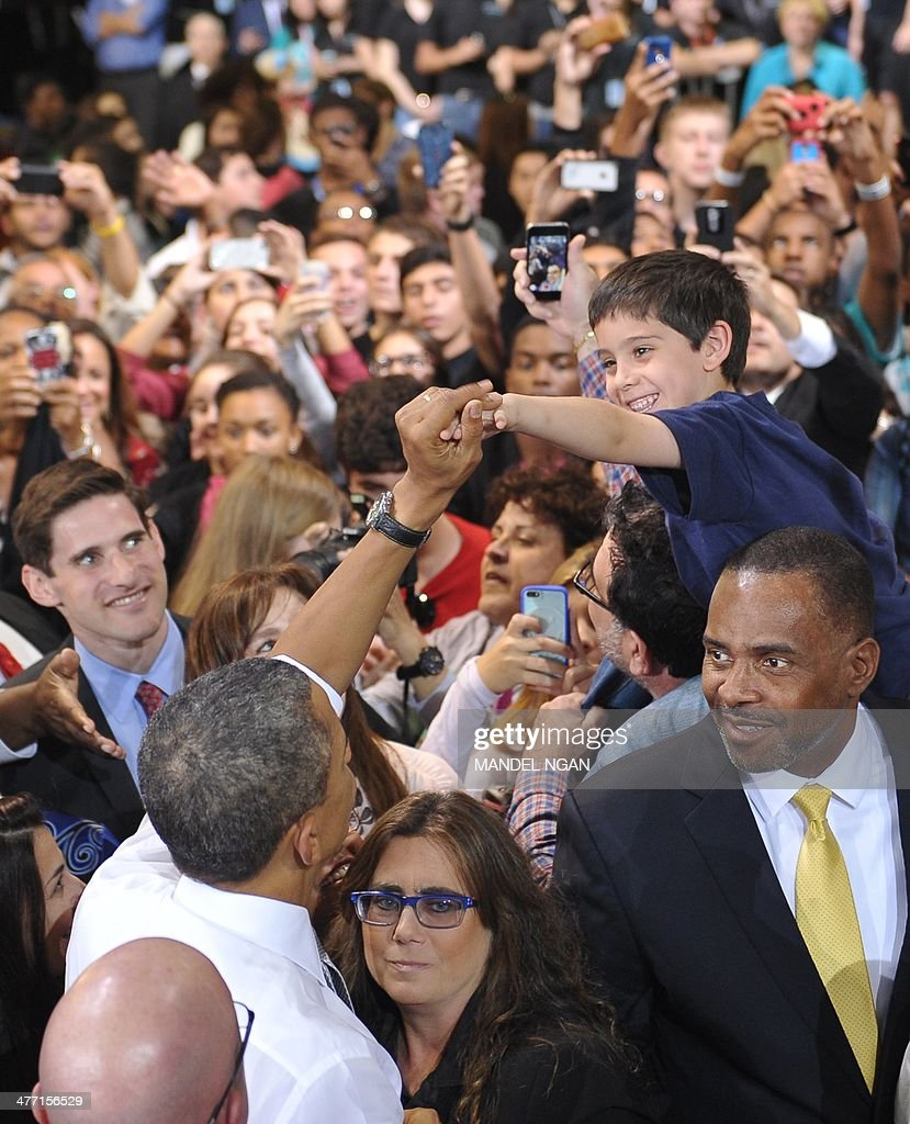 US President Barack Obama greets a young boy after speaking at Coral Reef High School in Miami, Florida on March 7, 2014. AFP PHOTO/Mandel NGAN