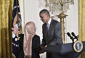 US President Barack Obama greets Aisha Osman of Beaverton Oregon who introduced him as he arrives for an Eid alFitr reception in the East Room of the...