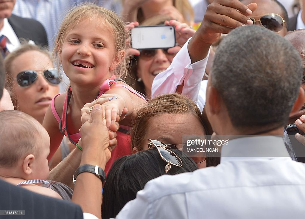 US President Barack Obama greets audience members after speaking on the economy at the Lake Harriet Band Shell in Minneapolis, Minnesota on June 27, 2014