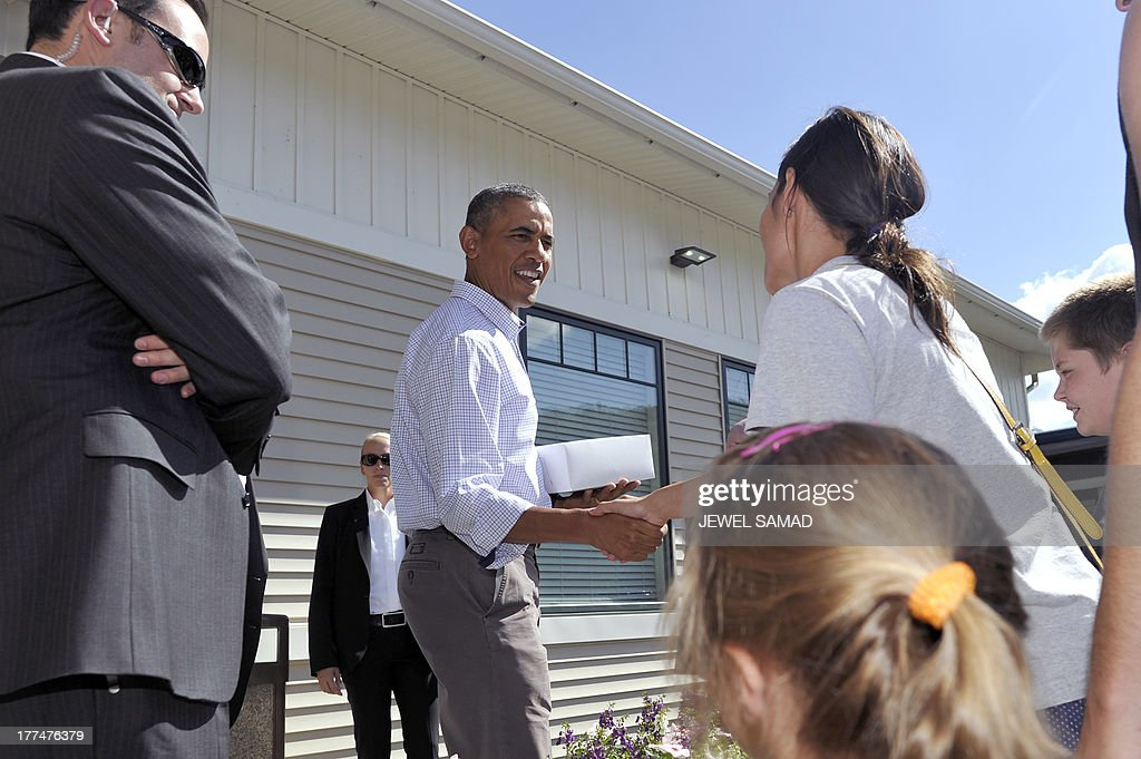 US President Barack Obama greets bystanders after buying pie from a local restaurant in Lenox, Pennsylvania, on August 23, 2013. Obama is on a two-day bus tour through New York and Pennsylvania to discuss his plan to make college more affordable, tackle rising costs, and improve value for students and their families. AFP Photo/Jewel Samad
