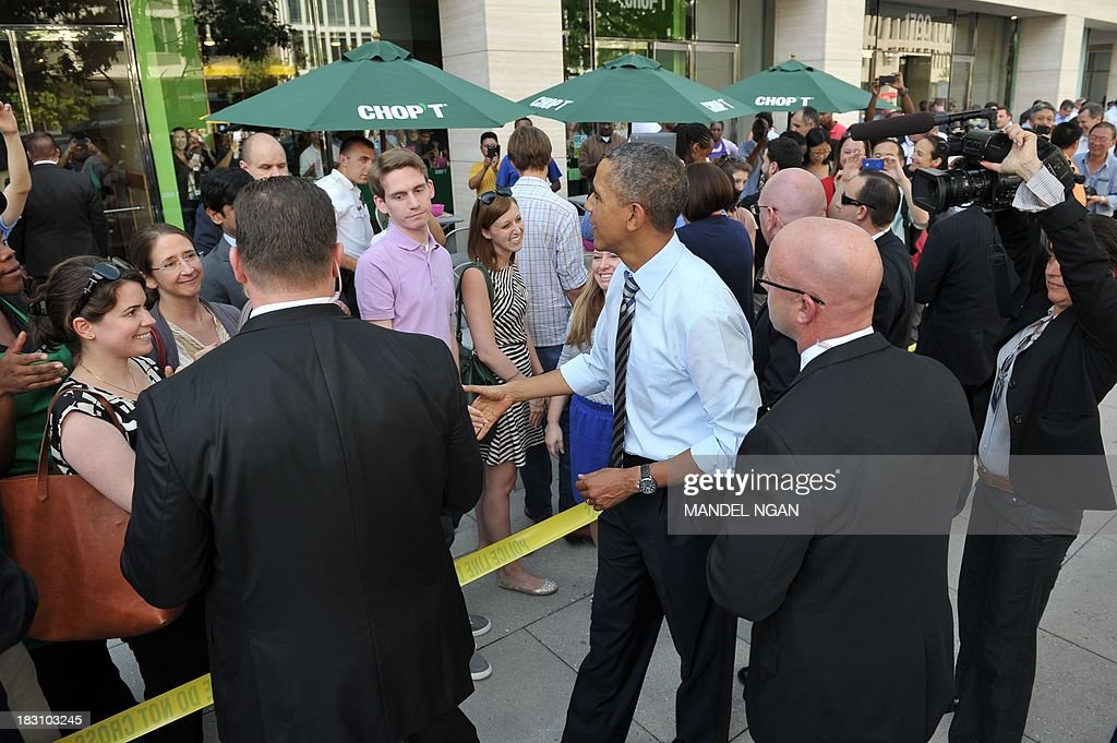 US President Barack Obama greets bystanders after picking up lunch at Taylor Gourmet Deli on Pennsylvania Ave in Washington, DC on October 4, 2013. Obama walked over to the deli with US Vice President Joe Biden and ordered sandwiches to go. AFP PHOTO/Mandel NGAN