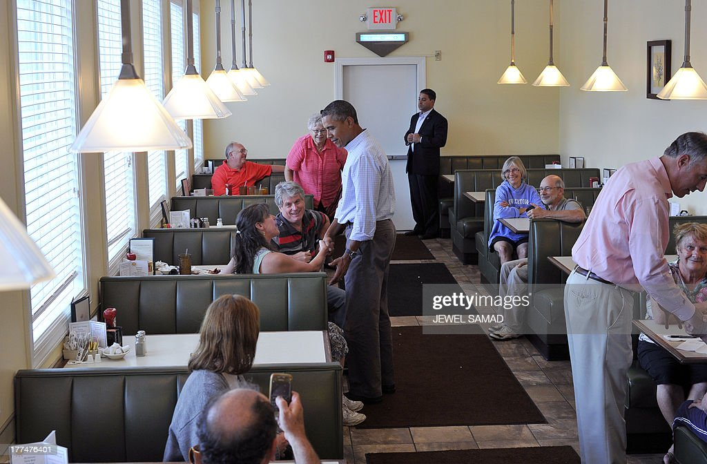 US President Barack Obama greets dinners after ordering pie at a local restaurant in Lenox, Pennsylvania, on August 23, 2013. Obama is on a two-day bus tour through New York and Pennsylvania to discuss his plan to make college more affordable, tackle rising costs, and improve value for students and their families. AFP Photo/Jewel Samad